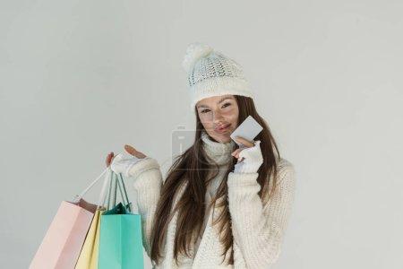 Photo pour Belle femme en pull en hiver à la mode et écharpe debout avec des sacs à provisions et carte vide isolé sur blanc - image libre de droit