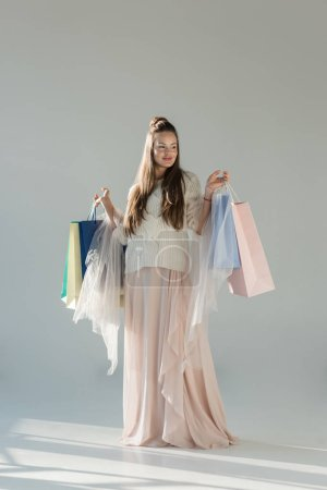 cheerful attractive woman in fashionable winter outfit standing with shopping bags on white
