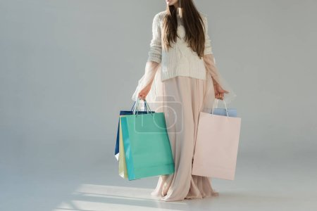 cropped image of woman in fashionable winter outfit standing with shopping bags on white