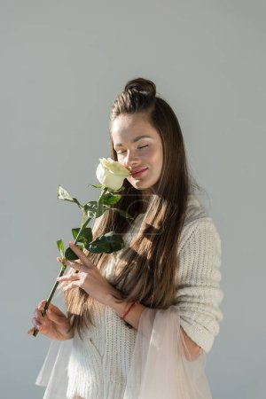 attractive woman in fashionable winter outfit sniffing white rose with closed eyes isolated on white