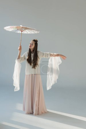 attractive woman in stylish winter outfit standing under japanese umbrella on white