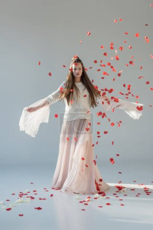 beautiful woman in fashionable winter outfit spinning around under falling red roses petals on white