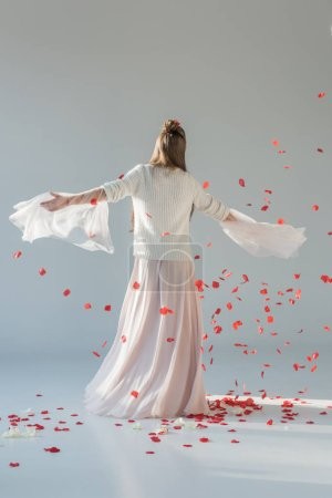 back view of attractive woman in fashionable winter outfit spinning around under falling red roses petals on white