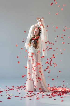 attractive woman in fashionable winter outfit standing with closed eyes under falling red roses petals isolated on white