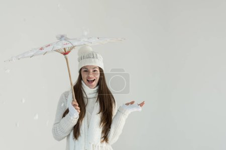 excited woman in fashionable winter sweater and scarf standing under japanese umbrella isolated on white