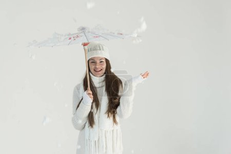 happy attractive woman in fashionable winter sweater and scarf standing under paper umbrella, snow falling isolated on white