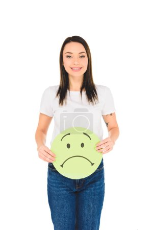 attractive girl holding green sign with sad face expression while looking at camera isolated on white
