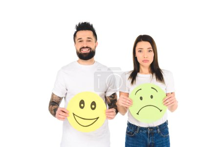 Photo for Young couple holding cards with happy and sad face expressions isolated on white - Royalty Free Image
