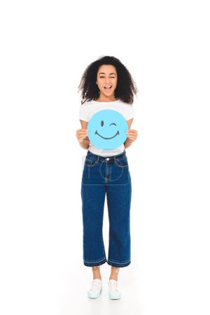 Photo for African american girl holding round, blue sign with winking face expression and smiling at camera isolated on white - Royalty Free Image