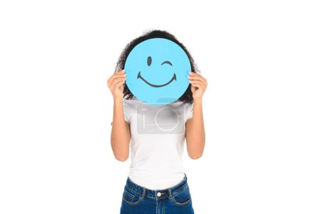 Photo for African american girl holding round, blue sign with winking face expression isolated on white - Royalty Free Image