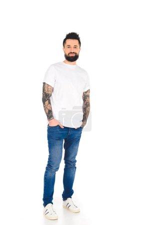 bel homme barbu avec des tatouages regardant la caméra et souriant isolé sur blanc