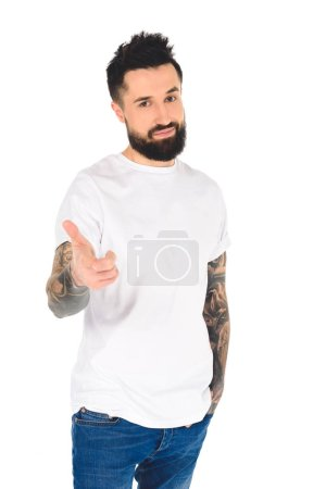 handsome bearded man with tattoos pointing with finger at camera isolated on white