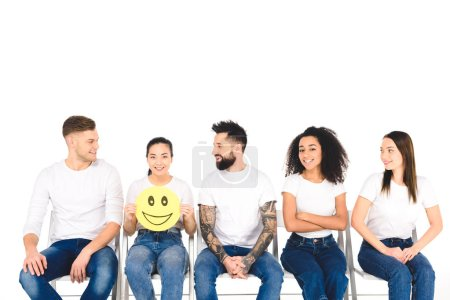 multicultural friends in white t-shirts looking at girl with happy sign isolated on white