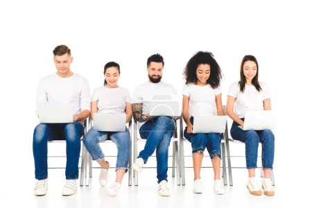 Photo for Multicultural cheerful group of young people using laptops isolated on white - Royalty Free Image