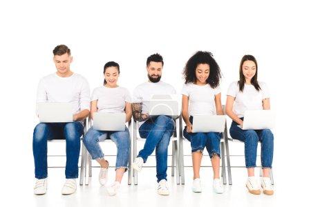 Foto de Grupo alegre multicultural de jóvenes que utilizan ordenadores portátiles aislados en blanco - Imagen libre de derechos