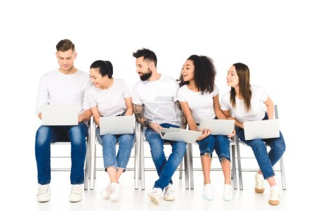 multicultural curious group of young people looking at laptop isolated on white