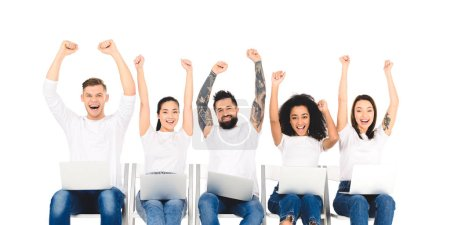 multiethnic group of people using laptops and rejoicing with hands above head isolated on white
