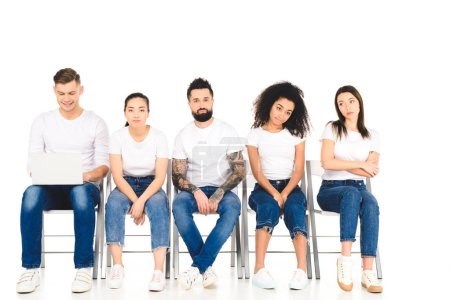 smiling man using laptop while sad multicultural group of people sitting on chairs isolated on white