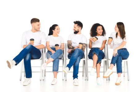 multicultural group of people sitting on chairs with coffee to go and speaking isolated on white