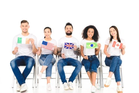 Photo for Multicultural group of people sitting on chairs with flags of different countries isolated on white - Royalty Free Image