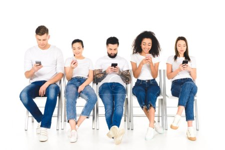 multicultural group of young people sitting on chairs with smartphones isolated on white