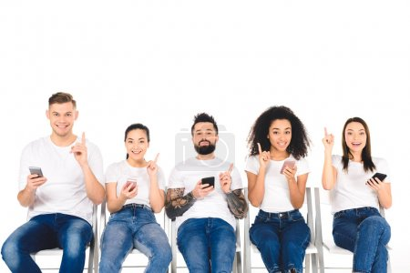 multicultural group of young people using smartphones and showing idea signs isolated on white