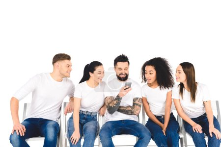 smiling tattooed man using smartphone while multiethnic curious young people looking at screen isolated on white