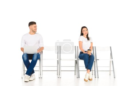 handsome man using laptop while young shy woman holding coffee to go isolated on white