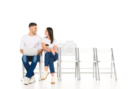 attractive girl sitting with coffee to go and flirting with handsome man isolated on white