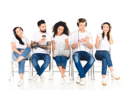multiethnic group of young people using gadgets while man holding coffee to go isolated on white