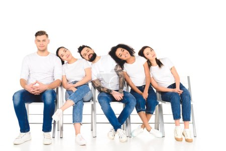 Photo pour Groupe multiculturel de jeunes couchés sur les épaules les uns des autres isolés sur blanc - image libre de droit