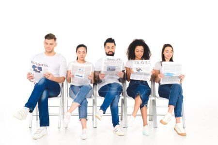 Photo for Multiethnic group of young people sitting on chairs with crossed legs and reading newspapers isolated on white - Royalty Free Image