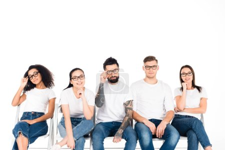 multicultural group of young people in glasses looking at camera isolated on white