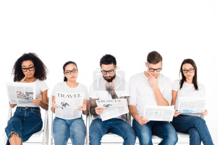 Photo for Multiethnic group of young people in glasses reading newspapers isolated on white - Royalty Free Image