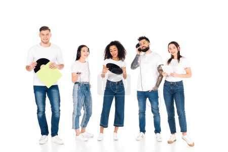 multicultural group of young people listening music in headphones and holding vinyl records isolated on white