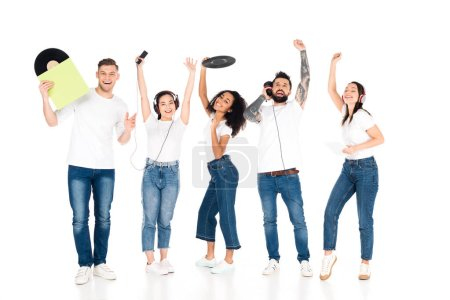 multicultural group of young people with raised hands listening music in headphones and holding vinyl records isolated on white