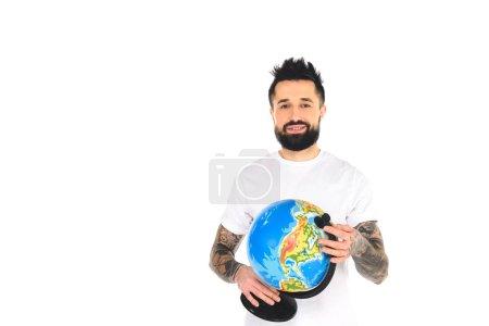 smiling bearded tattooed man holding globe isolated on white