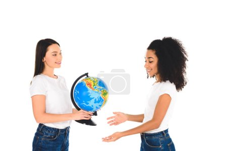 smiling woman holding globe near african american girl isolated on white