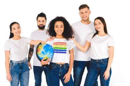 Photo pour Groupe multiethnique de jeunes gens touchant les épaules d'une femme afro-américaine avec signe lgbt sur t-shirt tenant globe isolé sur blanc - image libre de droit