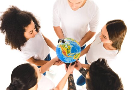 overhead view of multicultural group holding globe and standing in circle isolated on white