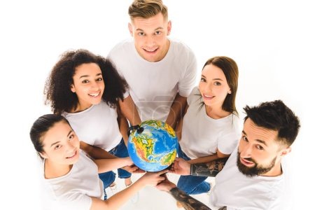 overhead view of multicultural group holding globe and smiling while standing in circle isolated on white