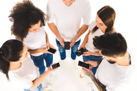 overhead view of multicultural group of people standing in circle and holding smartphones with blank screens in hands isolated on white
