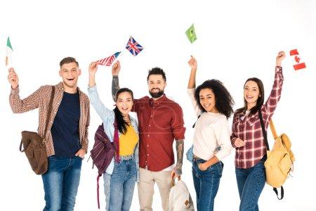 Foto de Grupo multiétnico de gente de pie con mochilas y banderas de diferentes países por encima de cabezas aisladas en blanco - Imagen libre de derechos