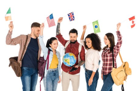 multiethnic group of people standing with backpacks and looking at globe while holding flags of different countries above heads isolated on white