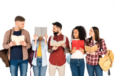 multicultural group of people holding backpacks and looking at girl with book isolated on white
