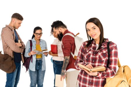 attractive girl holding book near group of young people isolated on white