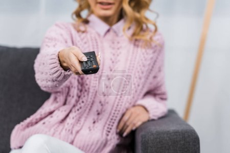 cropped view of woman sitting on sofa and changing channels with remote controller