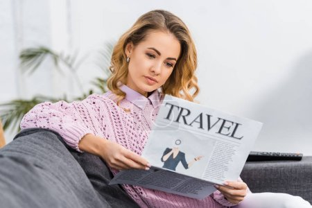 Photo pour Jolie femme assis sur le canapé et journal de voyage dans le salon de lecture - image libre de droit