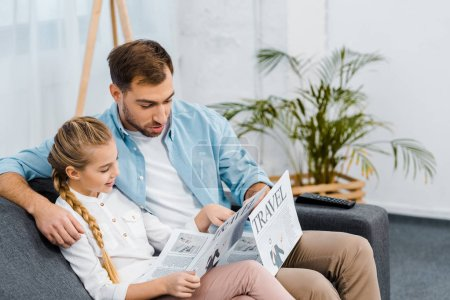 Photo for Handsome father and cute daughter sitting on sofa and reading travel newspapers in living room - Royalty Free Image