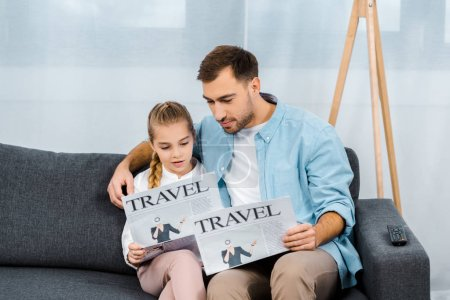 Photo for Father and daughter sitting on sofa and reading travel newspapers in living room - Royalty Free Image